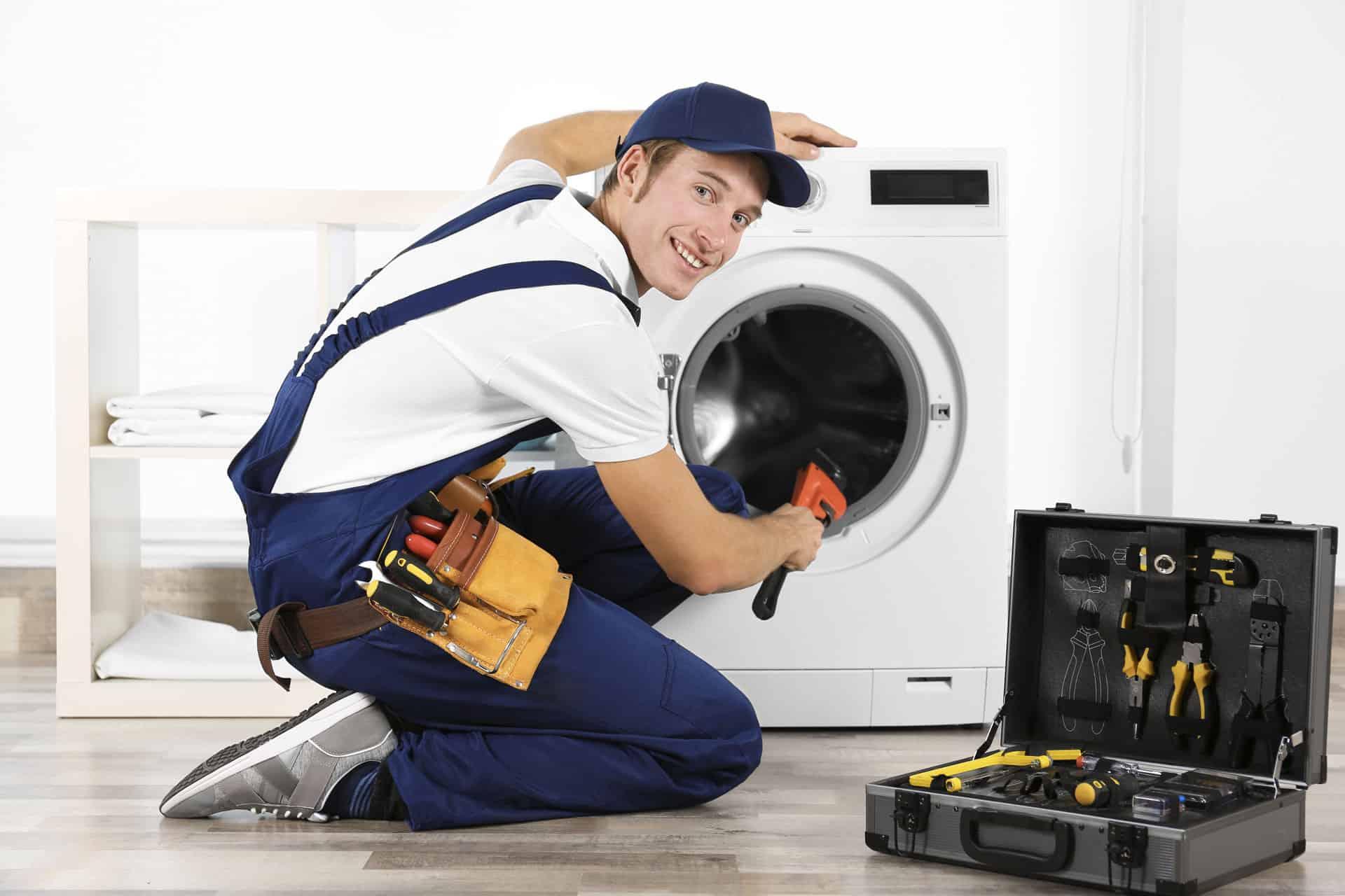 A smiling male mechanic fixing a washing machine
