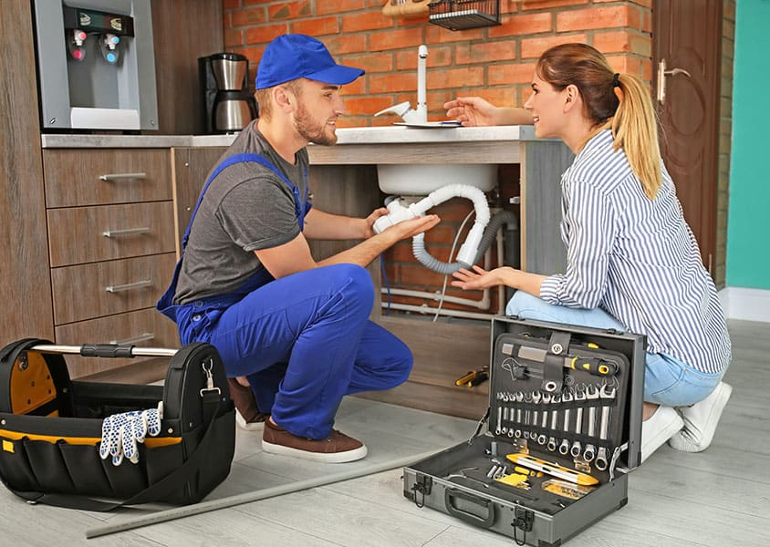 A male mechanic talking with a woman whilst fixing a kitchen sink pipe