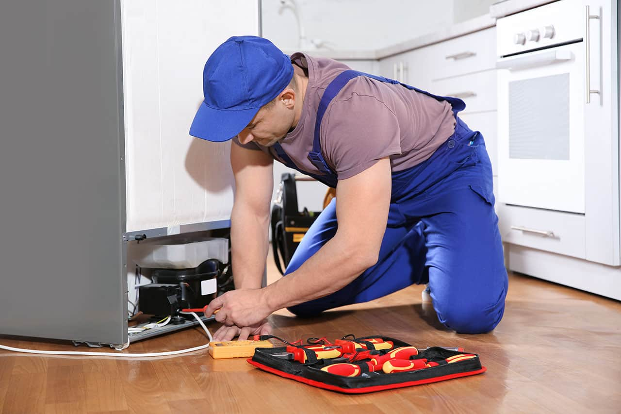 A male mechanic fixing the back of a refrigerator with tools