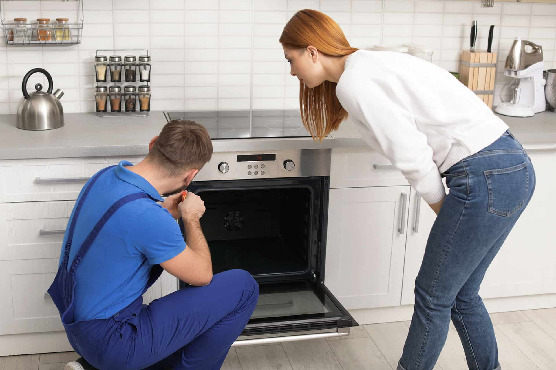A male mechanic fixing an oven with woman watching him