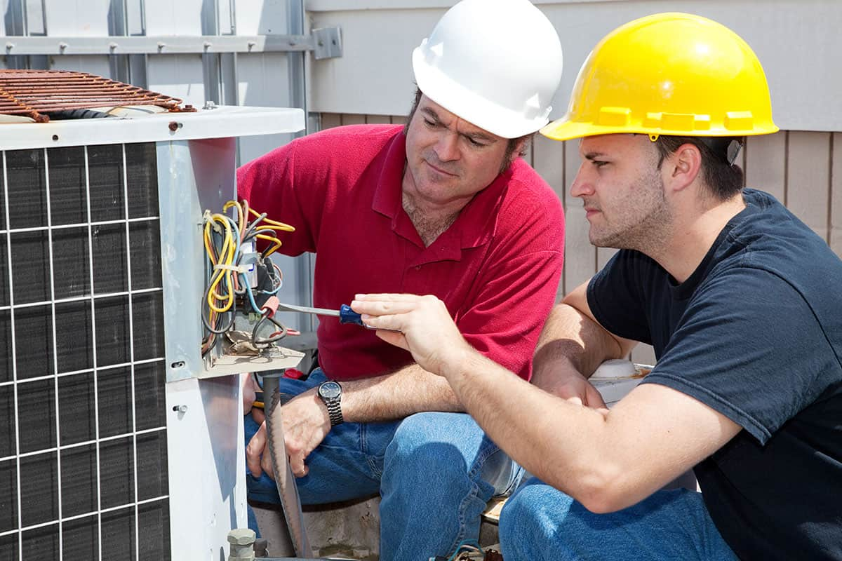 Two men with hard hats on fixing a ventilation system